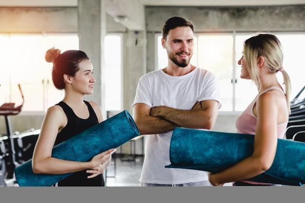 La giovane donna e gli uomini che preparano l'allenamento sano del corpo di stile di vita in palestra, mette in mostra il concetto di yoga di stile