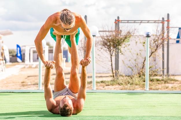 La giovane donna e gli uomini delle coppie sul campo che fa l'yoga di forma fisica si esercitano insieme. elemento acroyoga per forza ed equilibrio