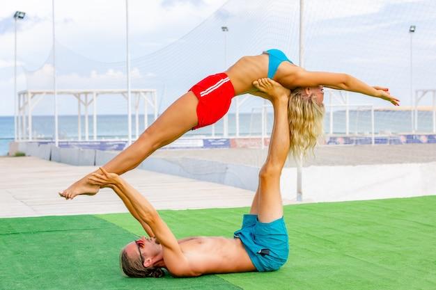 La giovane donna e gli uomini delle coppie sul campo che fa l'yoga di forma fisica si esercitano insieme.