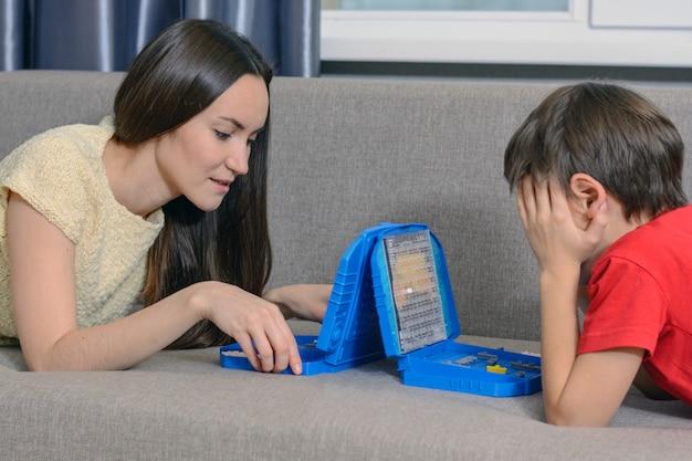 La giovane donna e il ragazzo che giocano un gioco di battaglia navale, si trovano sul divano nella stanza