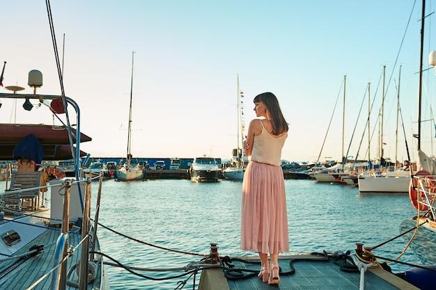 La giovane donna è in piedi sullo sfondo di bellissimi yacht
