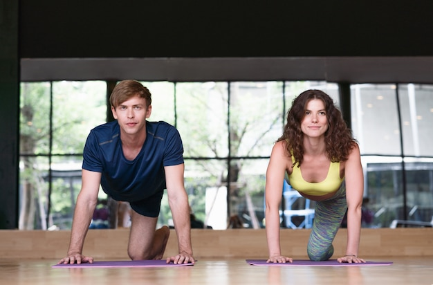 La giovane donna e l'uomo pratica esercizi di yoga al coperto a forma fisica