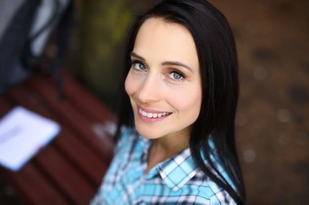 La giovane donna è seduta sulla panchina e sorridente