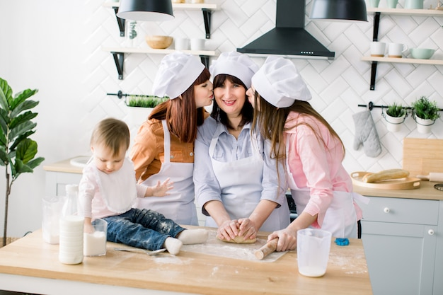 La giovane donna e sua sorella, la donna di mezza età e la piccola figlia carina che preparano la pasta, cuociono i biscotti alla festa della mamma. le figlie stanno baciando sua madre