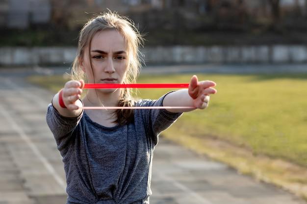 La giovane donna esile in abiti sportivi che fanno gli edifici occupati si esercita con l'elastico su una pista rivestita nera dello stadio