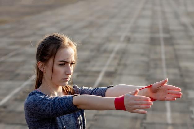 La giovane donna esile in abiti sportivi che fanno gli edifici occupati si esercita con l'elastico