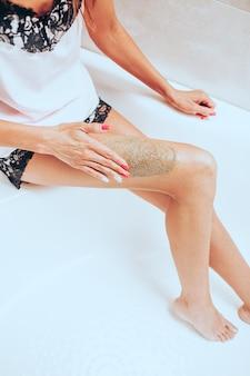 La giovane donna esile in un pigiama di seta brillante si raschia la gamba seduta in un grande bellissimo bagno luminoso