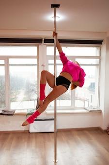 La giovane donna esile sbalorditiva esegue la danza del palo e mostra la sua figura adatta nello studio. giovane donna latina che allunga e si scalda per la sua lezione di fitness su palo.