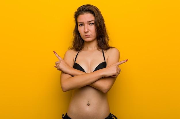 La giovane donna europea che indossa bikini punta lateralmente, sta cercando di scegliere tra due opzioni.