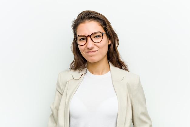 La giovane donna europea di affari scrolla le spalle le spalle e gli occhi aperti confusi.