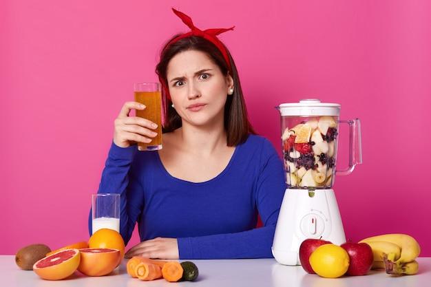 La giovane donna europea emozionale si siede al tavolo con attrezzatura da cucina, tenendo in mano un bicchiere di frullato di arancia