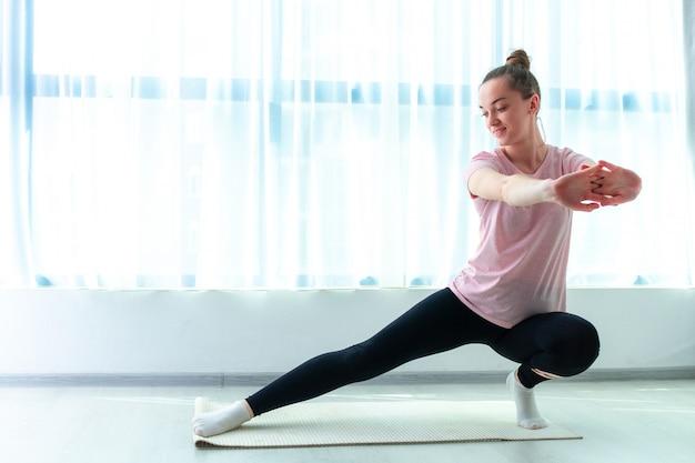 La giovane donna fa l'allungamento degli esercizi di forma fisica e del muscolo sulla stuoia di yoga a casa. perdere peso e mantenersi in forma. stile di vita sportivo sano