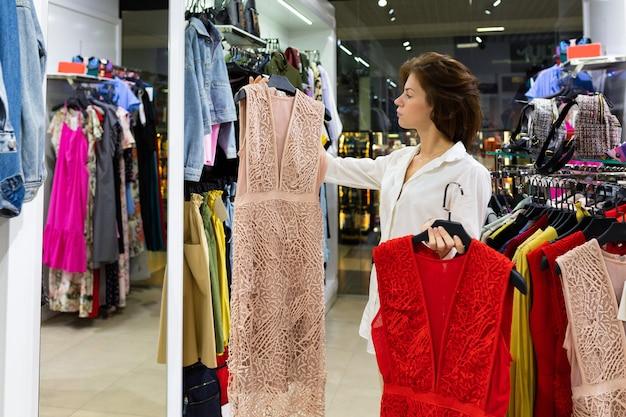 La giovane donna fa la scelta dell'outfit, con abito da sera beige in una mano e abito rosso nell'altra, in piedi nel negozio di abbigliamento alla moda