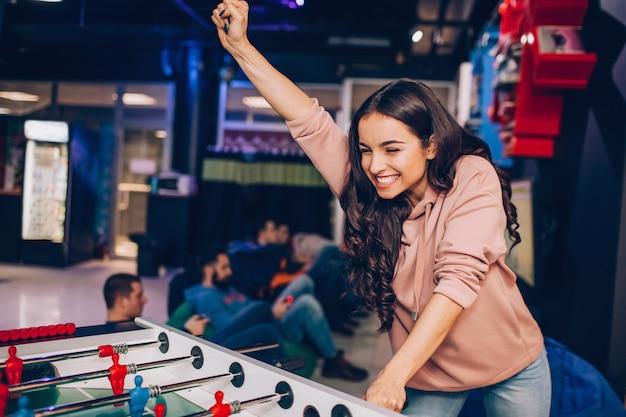 La giovane donna felice allegra sta nella sala e gioca a calcio-balilla. lei vince. modello tenere la mano in alto. suona da sola.