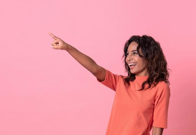 La giovane donna felice che il suo indicare consegna il fondo rosa dell'insegna