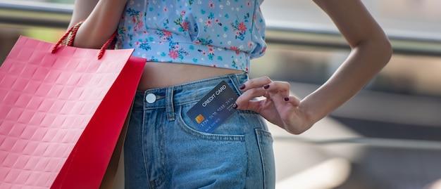 La giovane donna felice che tiene la carta di credito dalla tasca dei jeans con i sacchetti della spesa, spende i soldi con godendo allo shopping.
