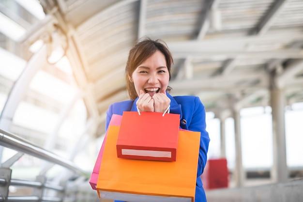 La giovane donna felice gode di con il sacchetto della spesa variopinto.