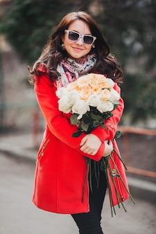 La giovane donna felice in cappotto luminoso con i fiori attraversa la città.