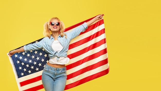 La giovane donna felice in denim copre giudicare la bandiera di usa isolata su fondo giallo
