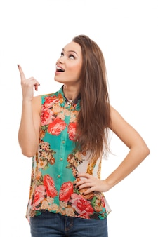 La giovane donna felice mostra su qualcosa