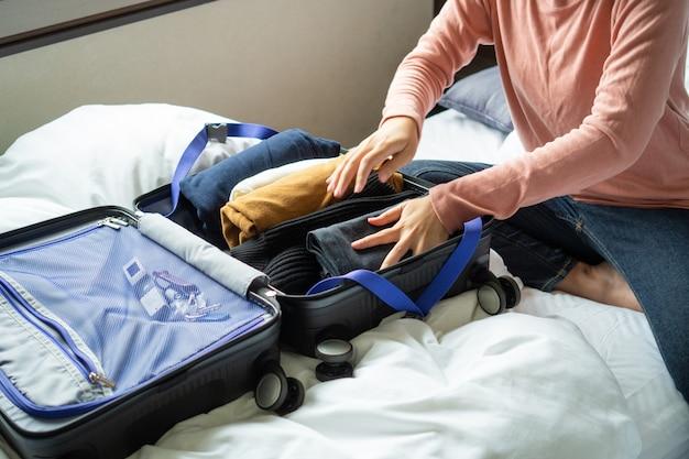 La giovane donna felice passa l'imballaggio dei vestiti nei bagagli di viaggio sul letto