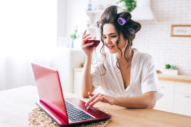 La giovane donna felice positiva tiene il vetro di vino rosso e lavora al computer portatile. sorridente. a casa da solo. stand in cucina. luce del mattino. vita negligente della governante.