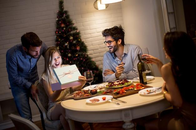 La giovane donna felice riceve il regalo dal giovane per il nuovo anno o il natale a casa