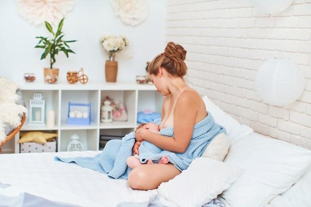 La giovane donna felice sta allattando al seno mentre si siede e abbraccia il suo bambino