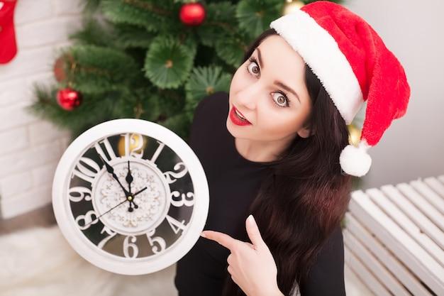 La giovane donna felice sta tenendo un orologio e sta sorridendo mentre celebrava il natale a casa