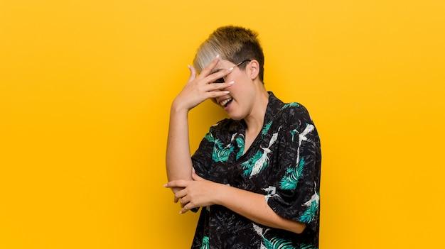 La giovane donna formosa che indossa un look estivo sbatte le palpebre alla telecamera attraverso le dita, la faccia coperta di imbarazzo.