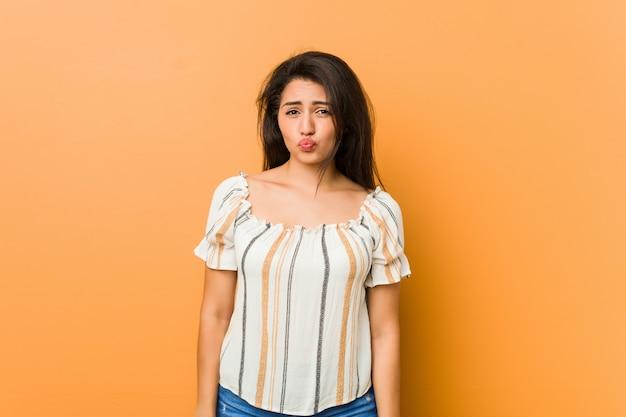 La giovane donna formosa soffia sulle guance, ha un'espressione stanca. concetto di espressione facciale.