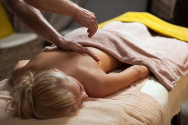 La giovane donna gode del massaggio in una stazione termale