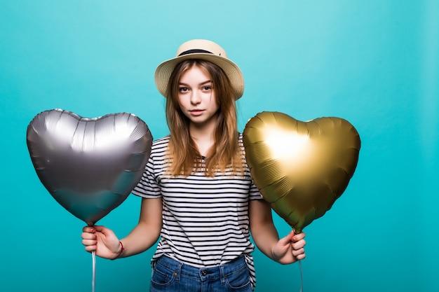 La giovane donna gode dell'occasione festiva che tiene i palloni metallici