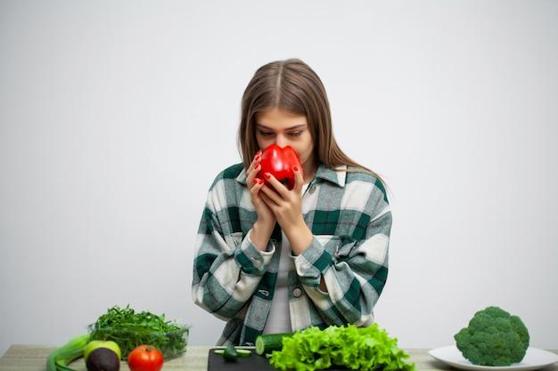 La giovane donna graziosa aderisce alla dieta e tiene le verdure