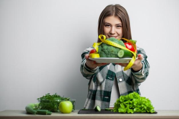 La giovane donna graziosa aderisce alla dieta e tiene un piatto di verdure