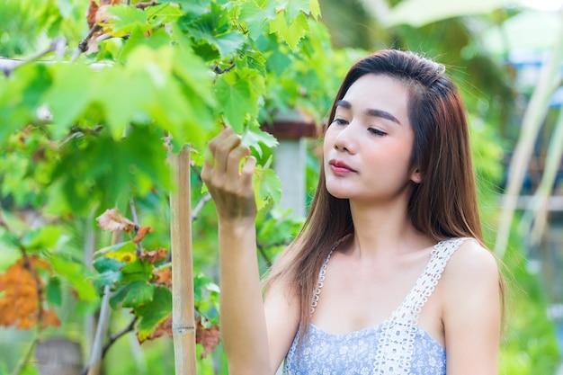 La giovane donna graziosa apprezza felicemente l'uva