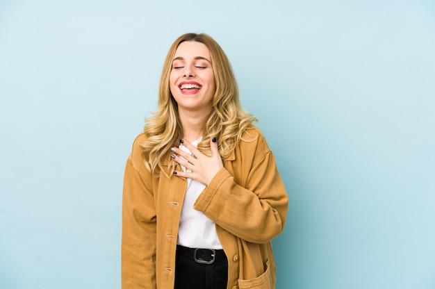 La giovane donna graziosa bionda isolata ride ad alta voce mantenendo la mano sul petto.