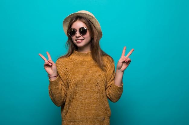 La giovane donna graziosa che indossa in cappello e occhiali da sole ha indicato il gesto di pace sulla parete blu