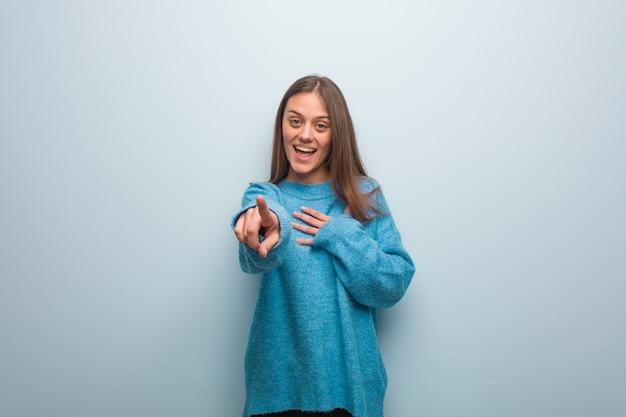 La giovane donna graziosa che indossa un maglione blu sogna di raggiungere obiettivi e scopi
