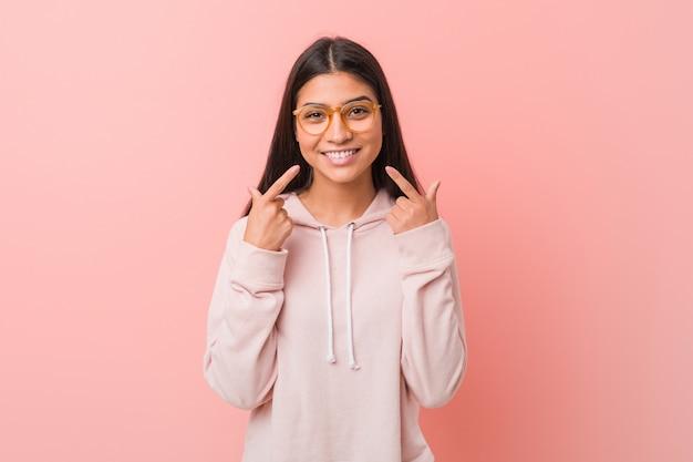 La giovane donna graziosa che indossa uno sguardo di sport casuale sorride, indicando le dita alla bocca