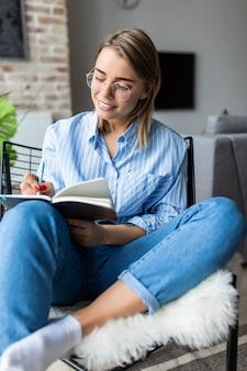 La giovane donna graziosa che legge o nota un libro e che si siede sulla sedia comoda a casa