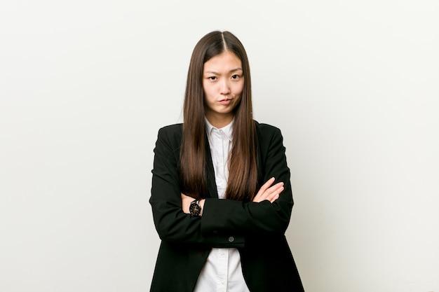 La giovane donna graziosa cinese di affari che aggrotta le sopracciglia nel dispiacere, tiene le braccia conserte