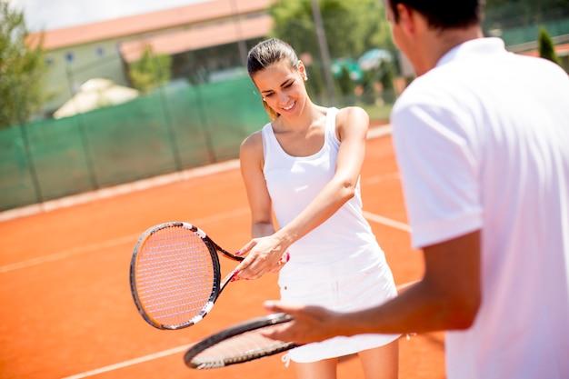 La giovane donna graziosa con il suo istruttore che pratica serve sul campo da tennis all'aperto