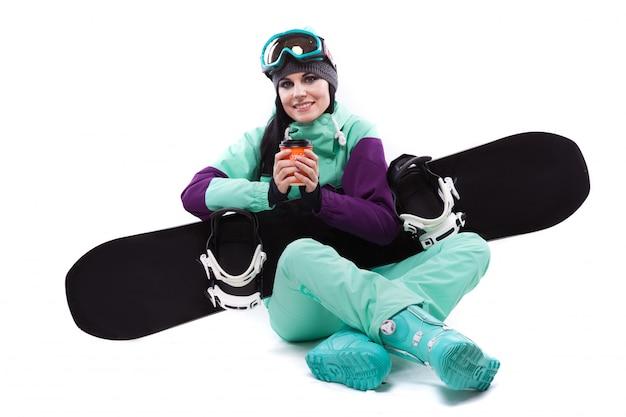 La giovane donna graziosa in costume da sci viola e occhiali da sci tiene snowboard nero
