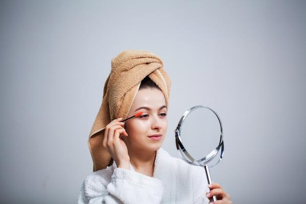 La giovane donna graziosa mette il trucco sul viso nel bagno
