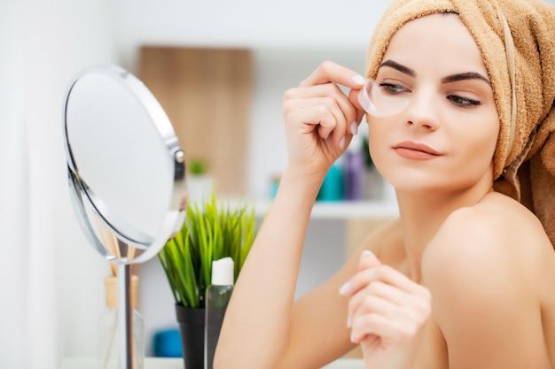 La giovane donna graziosa mette le toppe sotto gli occhi nel bagno