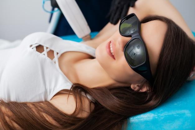 La giovane donna graziosa riceve la depilazione del laser per le gambe al salone di bellezza