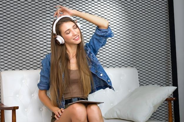 La giovane donna graziosa sta sedendosi sul sofà e sta indossando la cuffia per ascoltare la musica dalla compressa