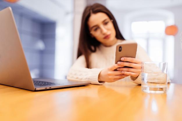 La giovane donna graziosa sta sedendosi sulla cucina con il computer portatile che ha videocall sul suo telefono