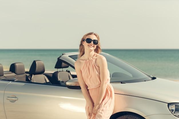 La giovane donna guida un'auto sulla spiaggia